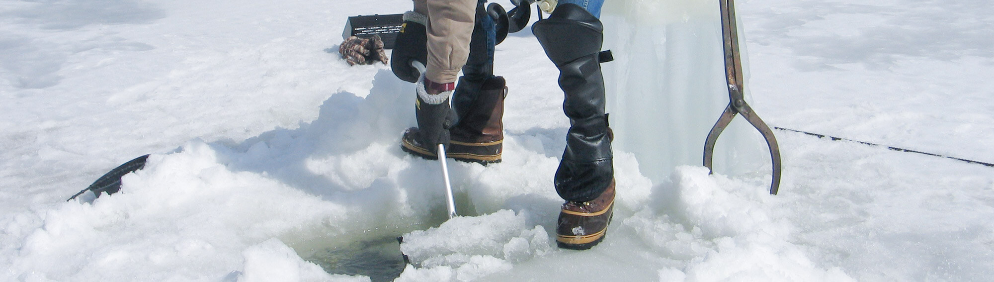 Ice fisherman using the Darkhouse Dipper to remove slush from a fishing hole